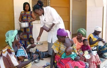 Distribution de spiruline par l'infirmiere dans le CREN de Nanorro, ou une ferme est presente dans l'enceinte meme de l'hopital. Les crens regroupent les enfants et leurs meres atteints de malnutrition. Nanorro, BURKINA FASO - 07/12/2005